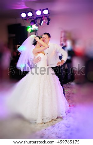 Happy couple of newlyweds dance, groom and bride dancing in restaurant - stock photo