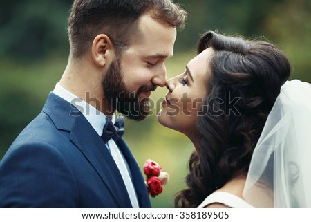 Happy couple of newlyweds looking at each other in a park closeup - stock photo
