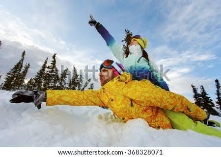 Happy couple of snowboarders having fun sitting in snowdrift  - stock photo