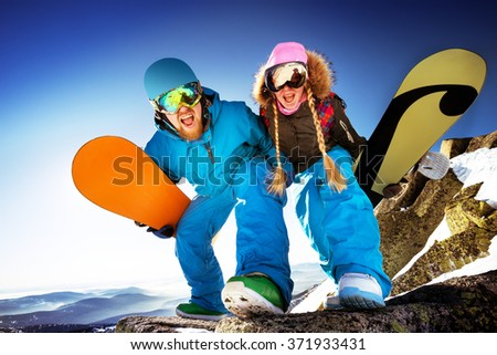 Happy couple of snowboarders stands on big rock on mountains backdrop