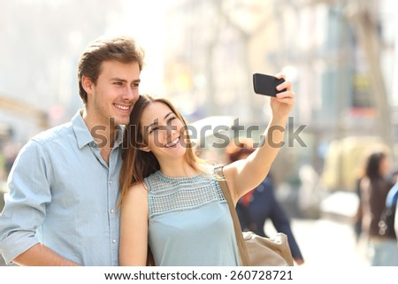 Happy couple of tourists photographing a selfie in a city street in a sunny day - stock photo