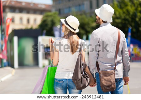 Happy couple of tourists shopping in the city - stock photo