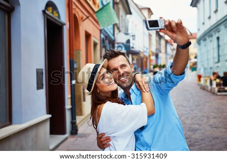 Happy couple of tourists taking selfie in old city - stock photo