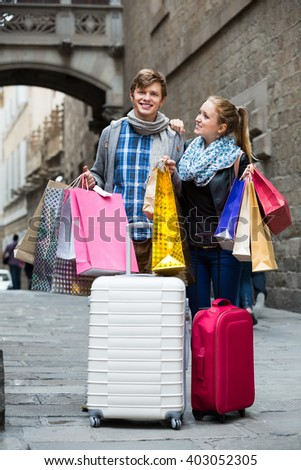 Happy couple of travellers with shopping bags at the city street