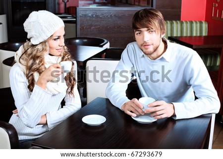 Happy couple of young people having a date at a caf - stock photo