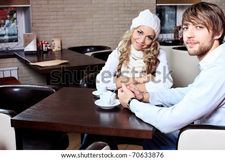 Happy couple of young people having a date at a cafe - stock photo