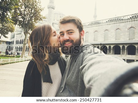 Happy couple of young tourists makes selfie photo near Blue Mosque in Istanbul, Turkey - stock photo