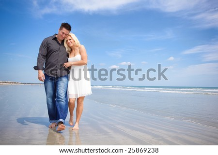 Happy couple on a beach walking - stock photo