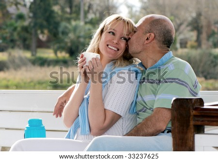 Happy couple on a bench in park - stock photo