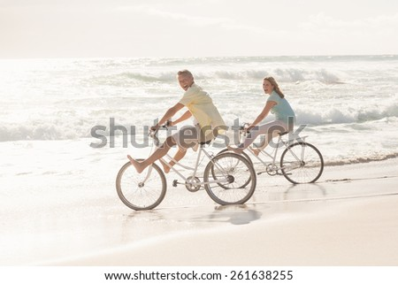 Happy couple on a bike ride at the beach - stock photo