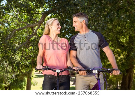 Happy couple on a bike ride on a sunny day - stock photo