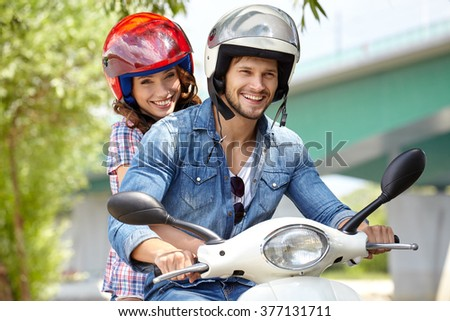 Happy couple on a scooter outdoors - stock photo