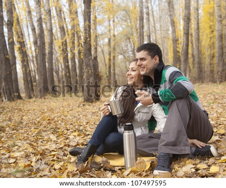 Happy couple on a yellow plaid  in autumn park looking in the far - stock photo