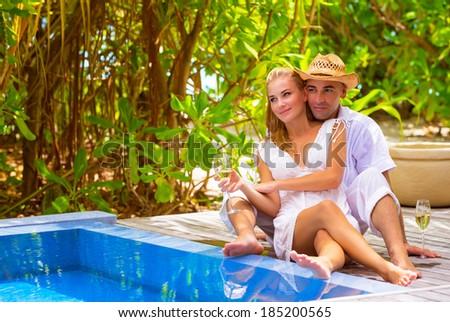 Happy couple on beach resort, sitting near pool and drink wine, luxury vacation on Maldives, romantic honeymoon, summer holidays concept - stock photo