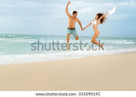 Happy couple on beach together jumping on beach  - stock photo