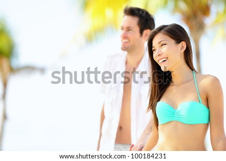 Happy couple on beach vacation travel walking under the sun on sunny summer day. Young beautiful interracial couple, Asian woman, Caucasian man. - stock photo