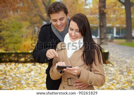 Happy couple on city trip navigating with smartphone