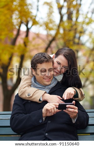 Happy couple on park bench using a smartphone - stock photo
