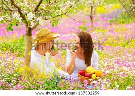 Happy couple on picnic in beautiful blooming garden, eating healthy organic food, romantic date, summer holiday and vacation concept  - stock photo