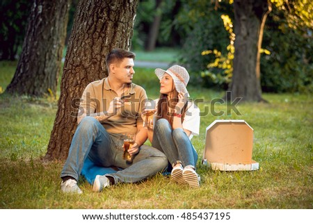 Happy couple on picnic in the park. Eating pizza and drinking beer.
