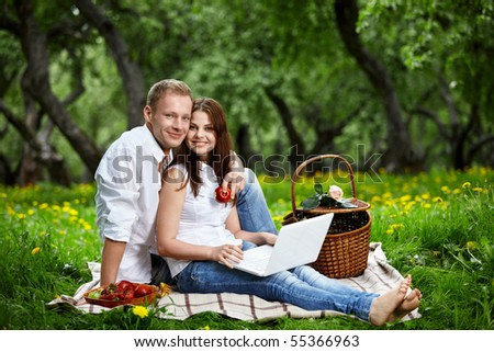Happy couple on picnic with the laptop in wood - stock photo
