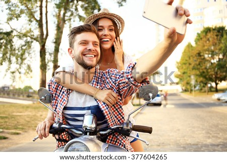 Happy couple on scooter making selfie photo on smartphone outdoors