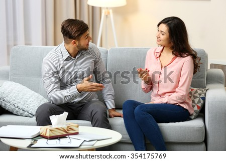 Happy couple on sofa, on home interior background