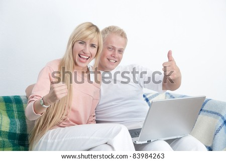 Happy couple on sofa with notebook