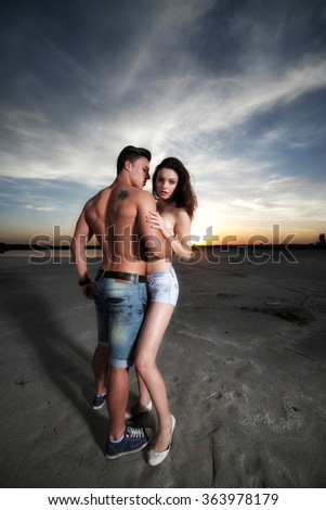 Happy couple on the beach. Cheerful couple embracing and posing on the beach. Fashion photo. - stock photo