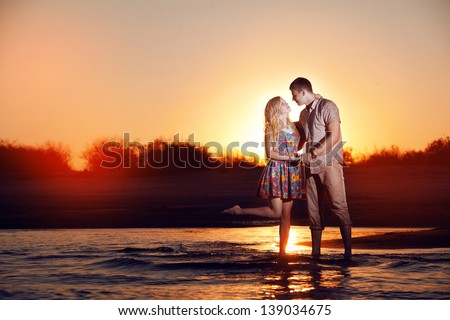 happy couple on the beach in the evening - stock photo