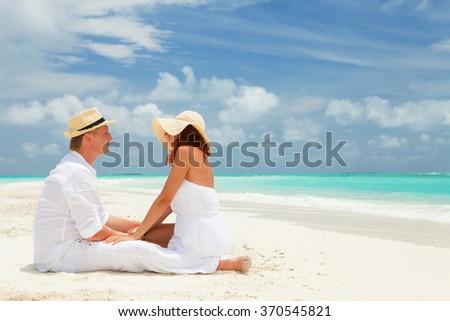 Happy couple on the beach of sea - stock photo