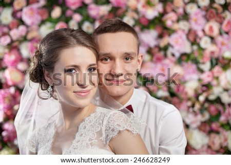 Happy couple on the flowers wall background - stock photo