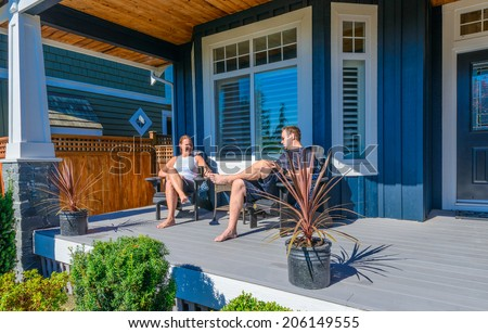 Happy couple on the porch of their house relaxing and enjoying sunny day. Vancouver, Canada. - stock photo