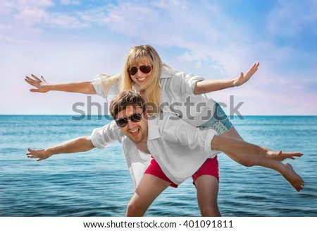happy couple on the sea guy keeps a girl on his back with his arms raised - stock photo