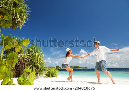 Happy couple on the tropical beach - stock photo