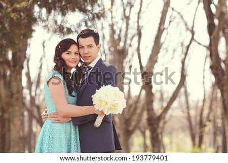 Happy couple on their ceremony day, bride holding peonies bouquet - stock photo
