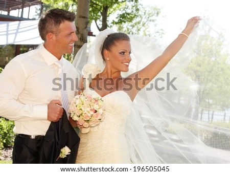 Happy couple on wedding-day, bride posing in wedding gown holding long veil. - stock photo