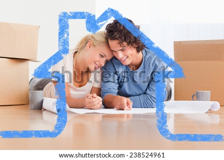 Happy couple organizing their new home against house outline - stock photo