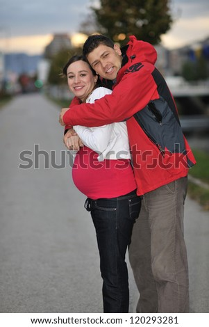 happy couple outdoor,  beautiful pregnant woman with her husband - stock photo