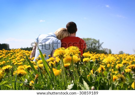 happy couple outdoors (dandelions in focus) - stock photo