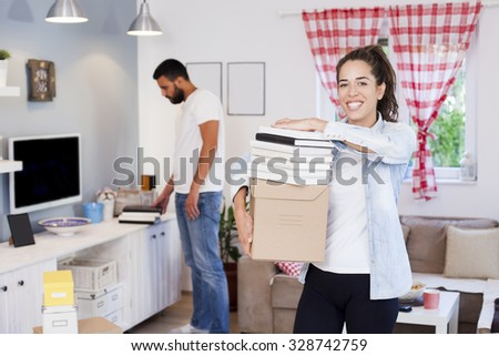 Happy couple packing cardboard boxes moving to new house Shallow depth of field