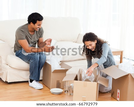 Happy couple packing glasses together in the living-room for their removal - stock photo