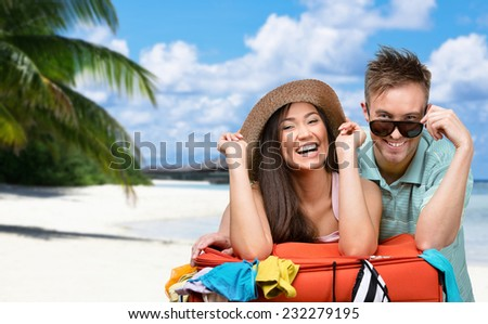 Happy couple packs up suitcase with clothing for trip, tropical island background. Concept of romantic vacations and lovely honeymoon - stock photo