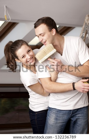 Happy couple painting a wall in their new home. Selective focus - stock photo