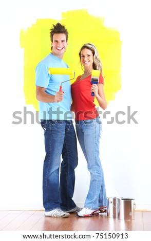 Happy couple painting interior wall of home. - stock photo