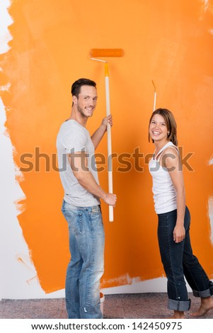 Happy couple painting the interior of their new house - stock photo