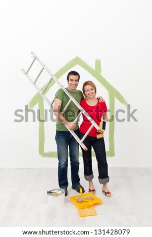 Happy couple painting their home - preparing the utensils - stock photo