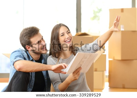 Happy couple planning decoration when moving home sitting on the floor - stock photo