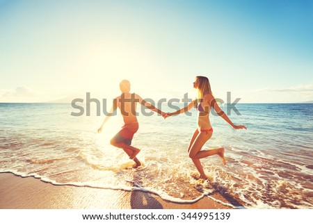Happy Couple Playing and Running on the Beach at Sunset  - stock photo