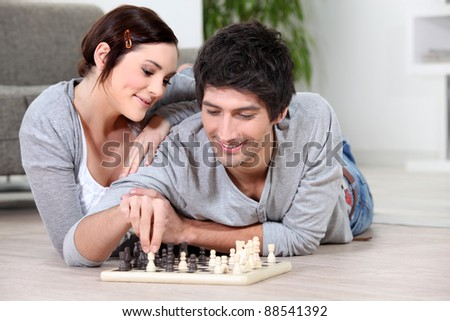 happy couple playing chess - stock photo